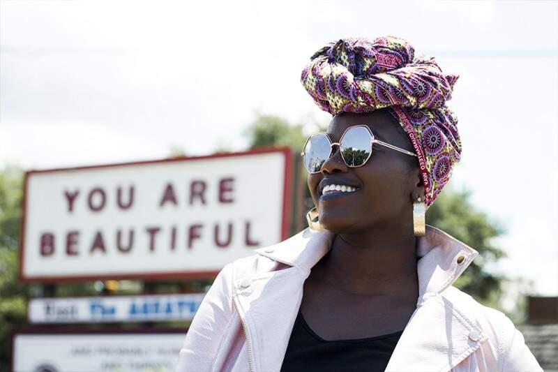 """autoconfiança mulher negra sorrindo olhando para o horizonte. Placa escrito """"You are beautiful"""" ao fundo."""
